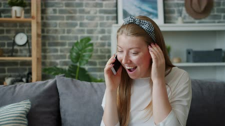 Excited teenager pretty girl is talking on mobile phone at home laughing discussing news enjoying gossip with friends. People, communication and house concept. Stockvideo
