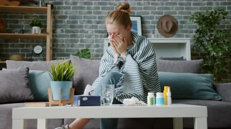 Young woman covered with blanket is coughing in paper tissue wiping nose feeling sick at home. Human health problems, treatment and lifestyle concept.