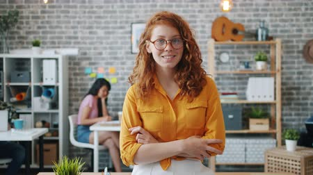 Portrait of beautiful female employee looking at camera and smiling standing in office with arms crossed. Happy people, successful business and workspace concept.