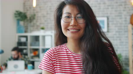 честолюбивый : Portrait of beautiful Asian girl in glasses looking at camera smiling in office room, people are working in background. Workplace and happy youth concept.