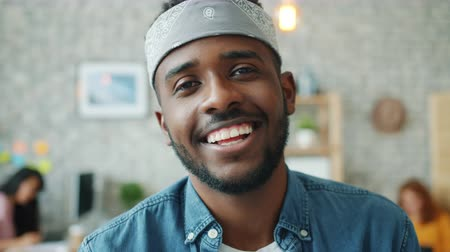 честолюбивый : Close-up portrait of cheerful African American guy smiling indoors in office looking at camera wearing casual clothing and accessories. Youth and job concept.