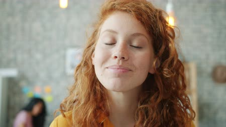 Close-up portrait of cheerful young woman with red curly hair smiling in office looking at camera while people working in background. Youth and work concept.