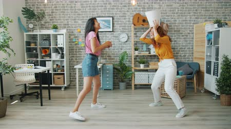 Happy young women office workers are having fun at work throwing paper in bin enjoying funny game together. Break, business and relaxation concept.