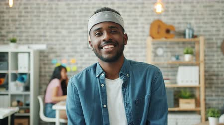 Portrait of joyful African American man in casual clothing smiling looking at camera in office indoors. Emotions, modern business and workplace concept.