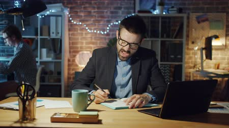 ziewanie : Tired businessman in suit is yawning working in office writing in notebook sitting at desk alone feeling exhausted. Workaholics, workplace and people concept.