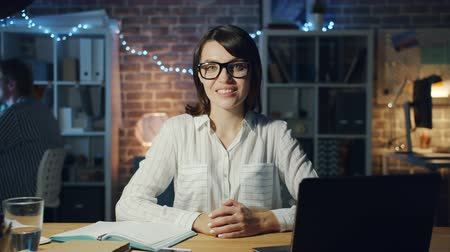 şahsiyet : Slow motion of beautiful business lady smiling in office at night sitting at desk looking at camera. Workplace, successful career and emotions concept.