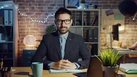 честолюбивый : Slow motion portrait of handsome guy office worker smiling in dark workplace looking at camera with happy face. Lifestyle, occupation and people concept. Стоковые видеозаписи