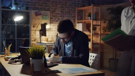 workload : Tired man is working in office late at night when female manager is bringing papers, guy is feeling unhappy and exhausted. Overwork, stress and lifestyle concept.