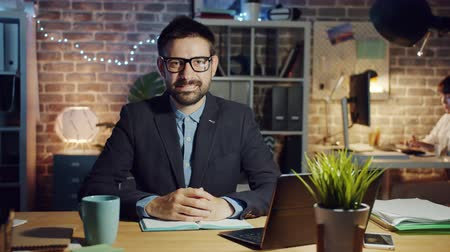 честолюбивый : Joyful businessman in glasses is smiling in office in the evening sitting at desk and looking at camera. Modern business, happy people and emotions concept. Стоковые видеозаписи