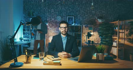 workload : Time lapse portrait of handsome young man sitting at desk in office looking at camera with serious face wearing glasses and jacket. People and workplace concept.