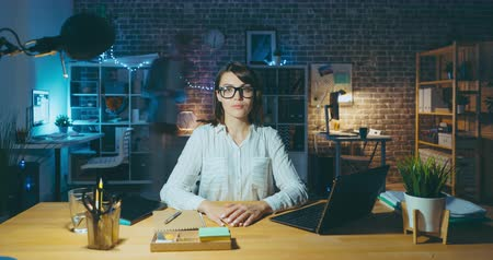 workload : Time lapse portrait of attractive girl office worker sitting at desk at night looking at camera with serious face while people are moving in background.