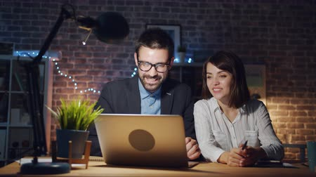 night together : Portrait of man and woman colleagues working with laptop in office talking smiling enjoying business communication. Technology and coworking concept. Stock Footage