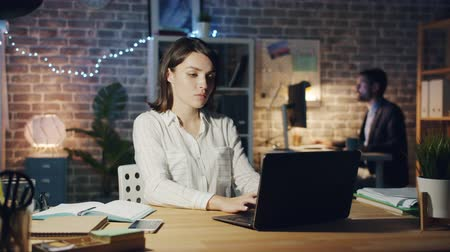 workload : Exhausted young lady is typing with laptop then lying on chair working in office at night being exhausted at work. Business, hard-working people and millennials concept.