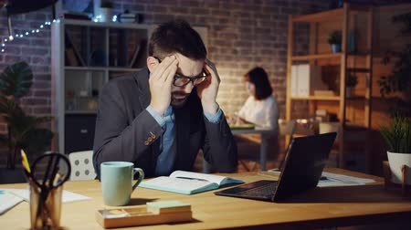 workload : Tired office worker is using laptop computer feeling headache sleeping on desk at night relaxing during work break. People, lifestyle and workaholics concept.