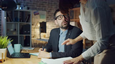 workload : Colleague young woman is bringing documents to tired office worker asking to finish paperwork, guy is feeling unhappy exhausted sitting at desk alone. People and job concept. Stock Footage