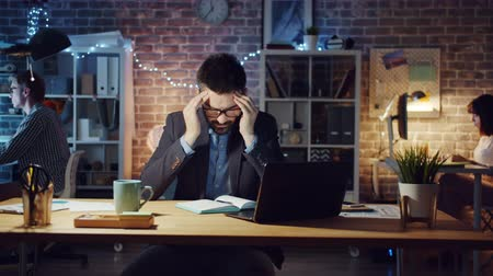 workload : Exhausted guy is feeling headache working with laptop in office at night then sleeping on desk relaxing at work. Deadline, workplace and modern people concept.