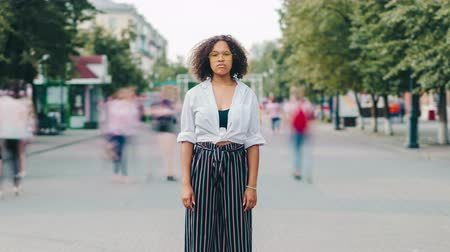 detenido : Zoom out time lapse portrait of African American lady in stylish clothing in pedestrian city street looking at camera with serious expression. Life and youth concept. Archivo de Video