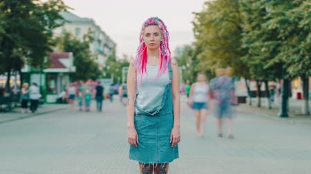 şahsiyet : Time lapse of punk girl with dyed hair and tattoo standing alone in flow of people in pedestrian street and looking at camera with serious face. Youth and style concept. Stok Video