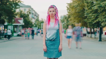 şahsiyet : Time lapse portrait of young woman student with dyed hair piercing and tattoo in city street looking at camera standing in crowd of people. Youth and lifestyle concept. Stok Video