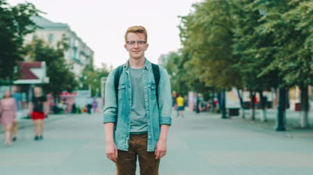 excesso de velocidade : Time lapse of attractive redhead guy with backpack standing in pedestrian street in city on summer day looking at camera. Lifestyle and modern people concept.