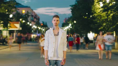 night life : Time lapse of attractive male hipster with tattoo standing in urban street in the evening looking at camera while crowd of people is rushing around. Lifestyle and city concept.