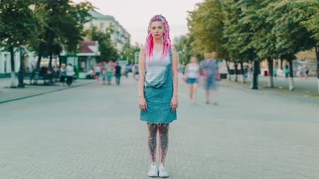 korhadt : Time lapse of beautiful hipster girl with dyed hair and tattoo looking at camera outdoors standing alone among flow of pedestrians. Modern lifestyle and loneliness concept.