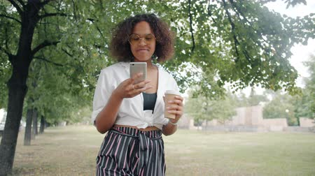 Cheerful African American lady is using smartphone walking with to go coffee in city park touching screen enjoying social media. Youth and leisure activities concept.