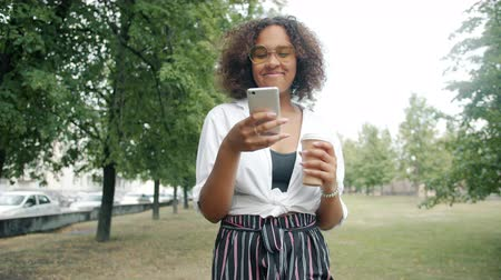 Afro-American woman is drinking coffee and using smartphone walking in city park alone enjoying leisure time, drink and modern technology. People and fun concept.