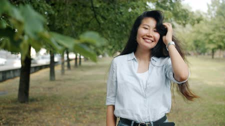 şahsiyet : Portrait of attractive Asian lady smiling touching hair looking at camera outdoors in city park on summer day. Modern lifestyle, people and nature concept.