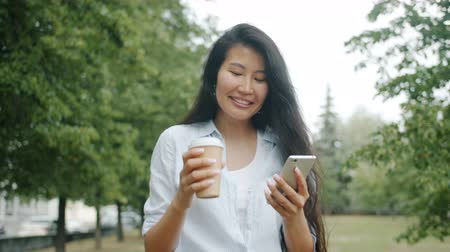 テイクアウェイ : Cute Asian girl student is walking in park with to go coffee and smartphone drinking enjoying social media touching screen. Youth and contemporary devices concept. 動画素材