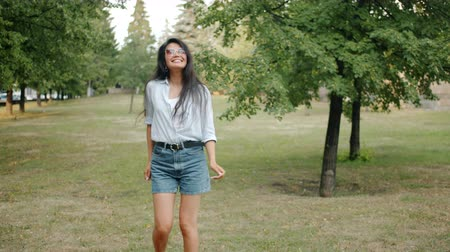şahsiyet : Slow motion of happy Asian girl in trendy clothing dancing in city park smiling enjoying leisure time and nature. People, lifestyle and happiness concept. Stok Video