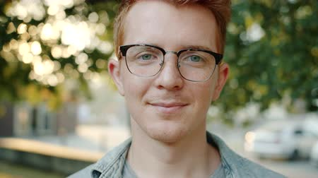 Close up slow motion portrait of attractive man student in glasses smiling outdoors in park looking at camera. Modern lifestyle and happy people concept.