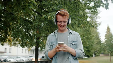 Happy young man in wireless headphones is walking in park listening to music using smartphone touching screen then looking around. Youth and leisure concept. Stockvideo