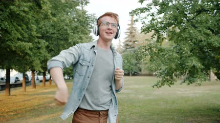 Cheerful student dancing outdoors in city park wearing headphones having fun alone enjoying music and leisure time. People and relaxation concept.