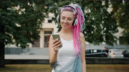 delici : Happy young lady hipster in headphones is dancing outdoors in park using smartphone enjoying music and summer nature. Youth culture and people concept.