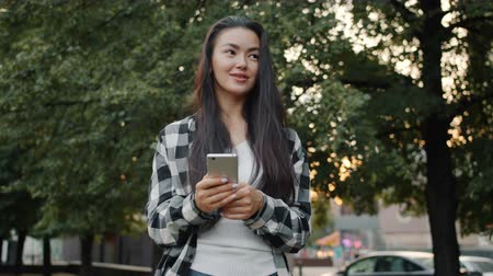 mensageiro : Cute Asian girl is touching smartphone screen in urban park standing alone smiling holding electronic device. Lifestyle, technology and communication concept.