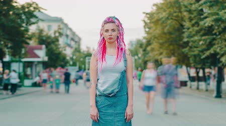 korhadt : Time lapse portrait of beautiful hipster girl with bright hair and tattoo outside in pedestrian street looking at camera. Youth culture, stylish people and city concept.