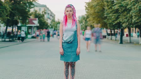 Time lapse portrait of cool young woman with colorful hair and tattoo standing in city street while people are moving around. Youth and modern style concept.