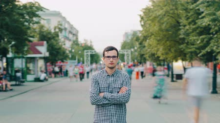 outsider : Time lapse porrait of young serious businessman in glasses outdoors in urban street with arms crossed looking at camera. Youth, city lifestyle and people concept. Stock Footage