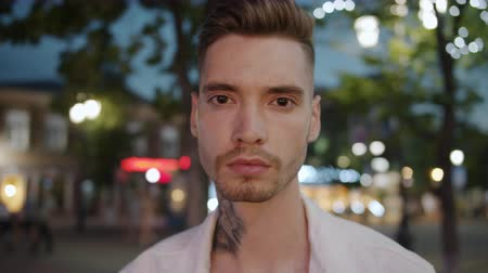 personalidade : Portrait of stylish guy with tattoo and trendy hairstyle standing in city street at night looking at camera. Youth and modern urban lifestyle concept. Stock Footage