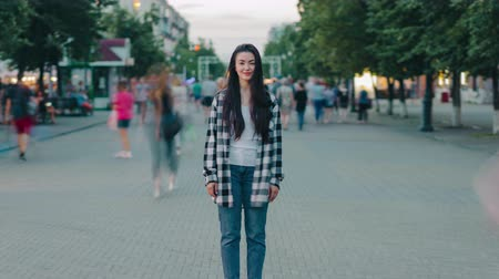 Zoom-in time lapse of beautiful young woman hipster standing outdoors in urban street smiling looking at camera while crowds of people are moving around. Stockvideo