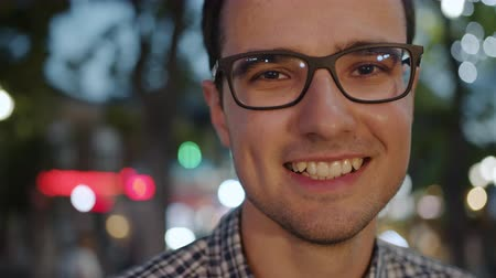 Close-up portrait of happy young brunet in glasses standing outdoors in the evening smiling looking at camera. Beaux hommes et concept d'émotions positives.