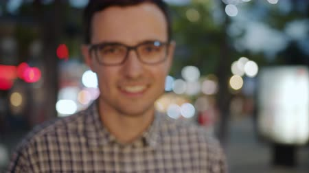 Zoom-in portrait of good-looking young guy in glasses smiling at camera in city street evening. Modern urban life and beautiful people concept. Stockvideo