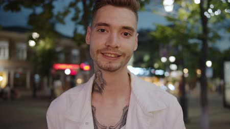 tattoo : Slow motion of cheerful hipster tattooed guy standing outdoors in urban street in the evening looking at camera alone. Youth and individual style concept.