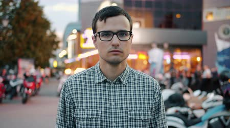 şahsiyet : Slow motion of serious young businessman in glasses standing alone in city street and looking at camera. Emotions, youth and summer evening concept. Stok Video