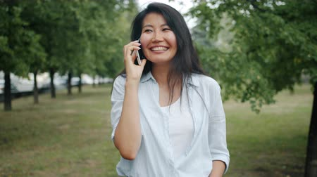 calling telephone : Asian student cute girl is talking on mobile phone laughing having fin in green park alone. Modern communication, happiness and conversation concept.