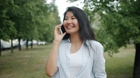 Joyful Asian woman student is chatting on mobile phone in green park in summer enjoying casual conversation outdoors. Youth and modern technology concept. Stockvideo