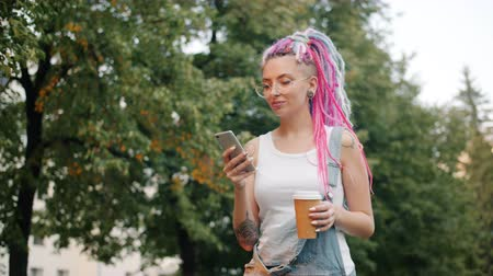 serseri : Cute girl punk with colorful hair is walking outdoors in park with smartphone and take out coffee smiling enjoying leisure time. People and lifestyle concept. Stok Video