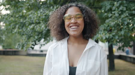 Slow motion of happy Afro-American girl laughing outdoors in urban park looking at camera standing alone. Positive emotions and young people concept. Stockvideo