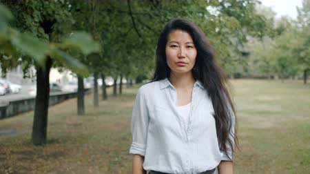 Portrait of serious young Asian businesswoman standing alone in city park looking at camera with confident face. Modern lifestyle and individuality concept.